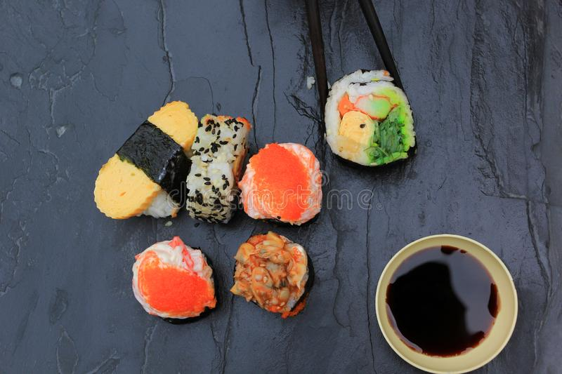 Japanese food, Top view of sushi set in chopsticks on stone dark stock photo