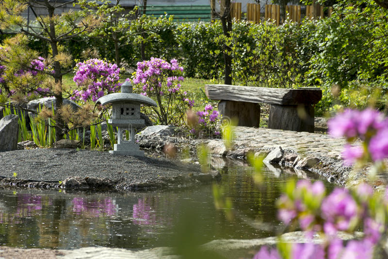Download Japanese Garden Bench Of Wood, A Pond, A Bush With Pink Flowers,
