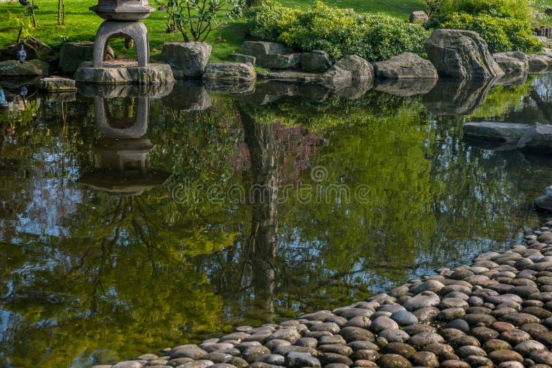 Japanese garden decorated with Japanese stone lanterns, flowers and stone floors stock image