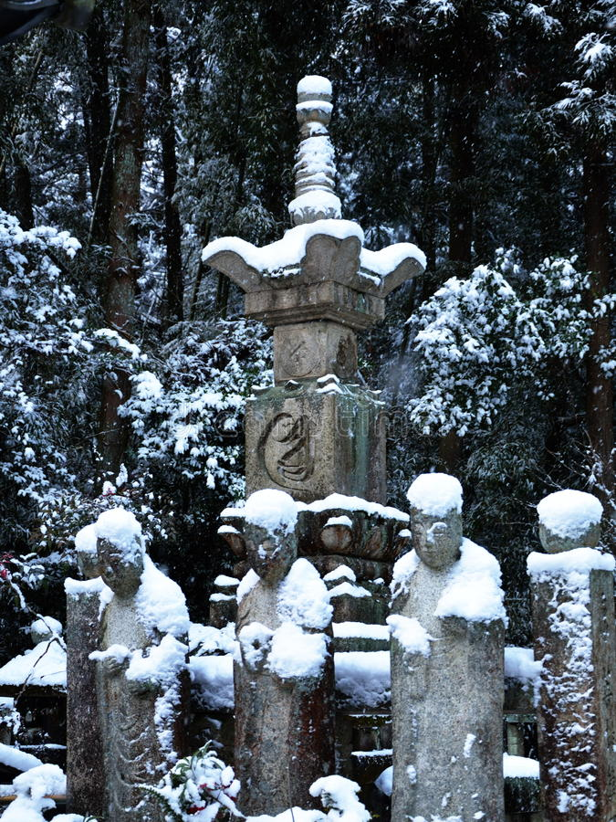 Old shrine and statues in Kyoto, winter. Snow falling on shrine, in ninnaji temple Kyoto Japan stock photography