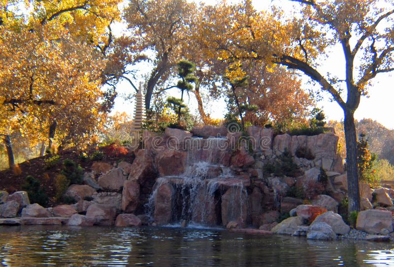 Japanese Gardens in early fall. At the botanical gardens in Albuquerque New Mexico. Waterfalls, oriental statues, Koi ponds and miniature bridges make up this stock image