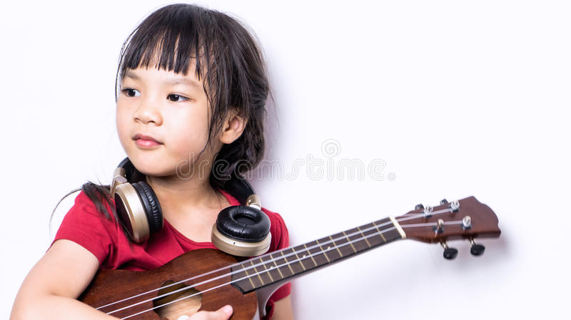 Japanese girl is playing guitar and wearing headphone. stock photography