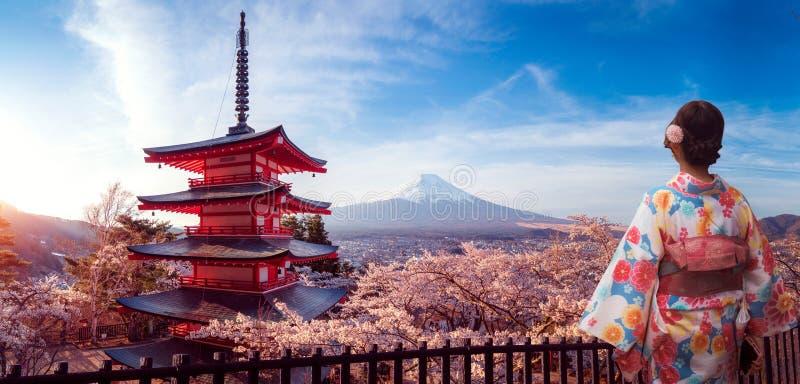 Japanese girl in kimono traitional dress walk in Sakura park with Fuji mountain background royalty free stock images