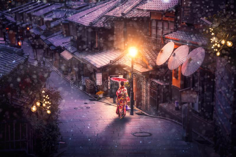 Japanese girl walk with traditional kimono dress in winter season. And use an umbrella for protect a snow in Kyoto city, Japan royalty free stock image