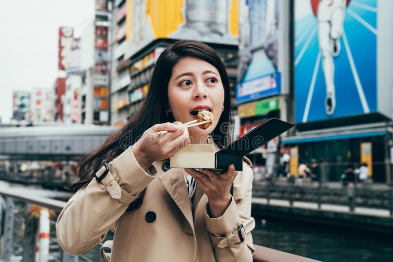 Japanese girl worker trying the tasty takoyaki. In the dotonbori near the river in osaka japan. young office lady eating local street food outdoor on sunny day royalty free stock photos