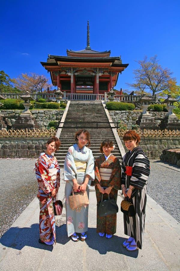 Japanese girls dressing traditional Kimono enjoy cherry blossom royalty free stock image