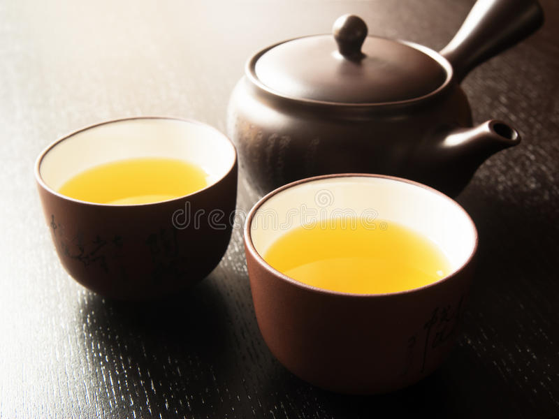 Japanese Green Tea. Japanese teapot and two cups filled with green tea on brown wooden background royalty free stock photography