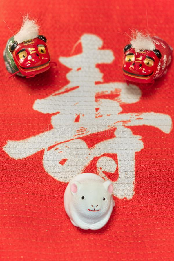 A Japanese greeting card with a cute rat figurine for the 2020 year of the mouse and two Folklore animals figurines. Depicting Shishimai lions on a red cloth royalty free stock images