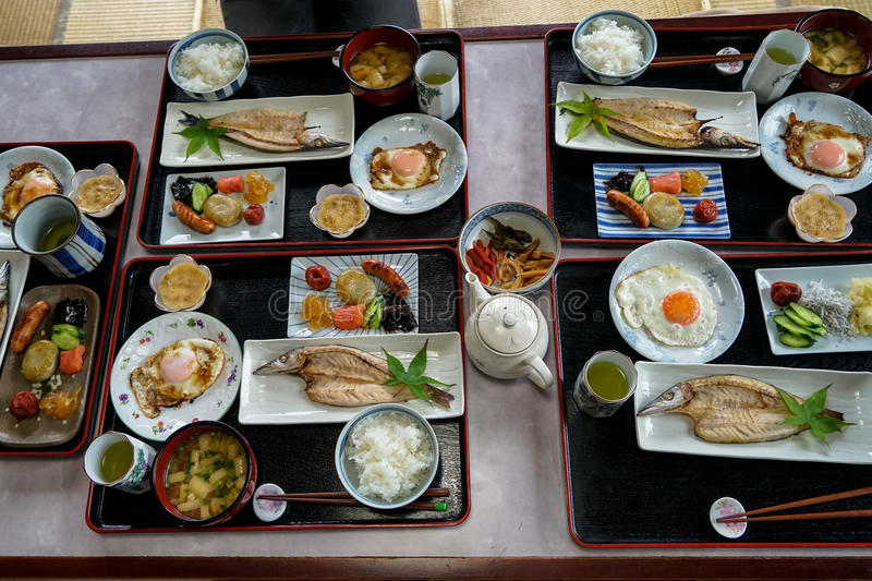 Japanese homestay breakfast tray including cooked white rice, grilled fish, fried egg, tofu soup, sausage, pickle, seaweed, etc. royalty free stock image