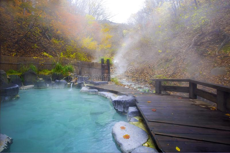Japanese Hot Springs Onsen Natural Bath Surrounded by red-yellow leaves. In fall leaves fall in Japan.Waterfall among many foliage stock photos