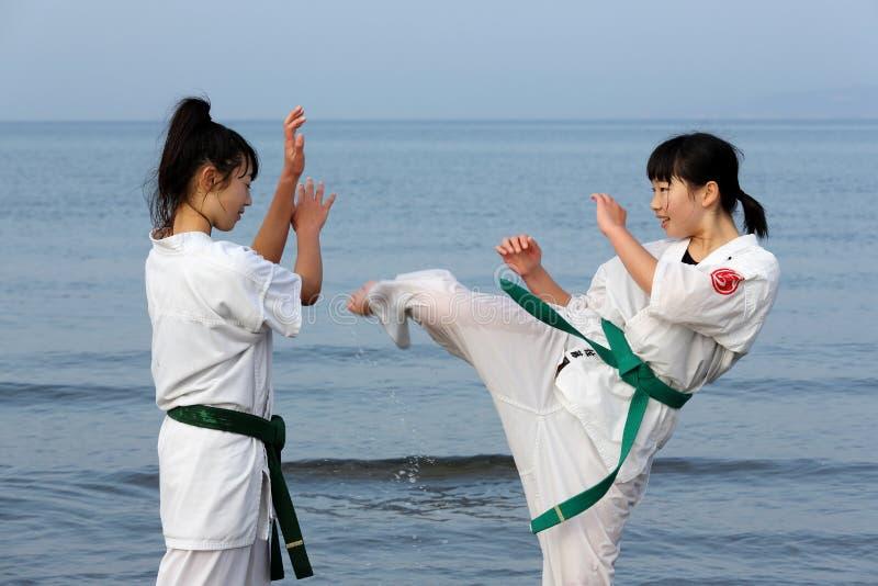 Japanese karate girls training at the beach. KAGAWA, JAPAN - Jan 3: Japanese karate girls training of karate in midwinter of a new year at Ichinomiya Beach royalty free stock image