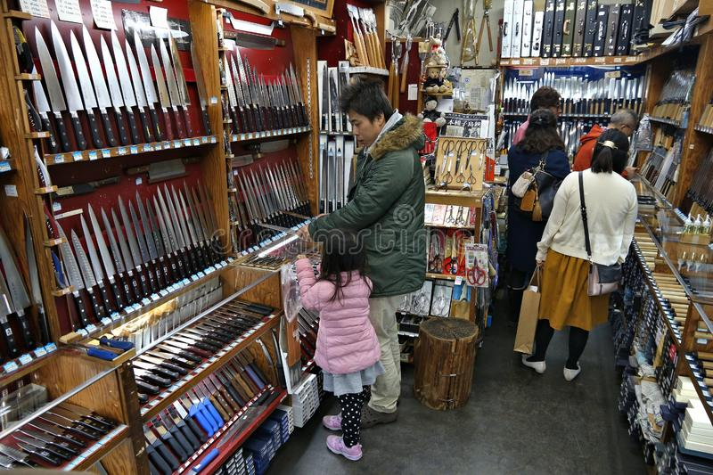 Japanese knife store. TOKYO, JAPAN - DECEMBER 4, 2016: Shoppers visit specialist knife store Kappabashi area of Asakusa in Tokyo, Japan. Kappabashi Street is royalty free stock photography