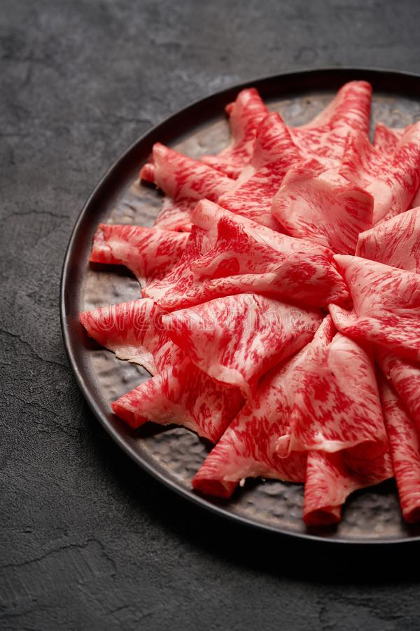 Japanese kobe beef sliced on ceramic plate on black background. Premium Japanese beef sliced on plate with black background stock photography