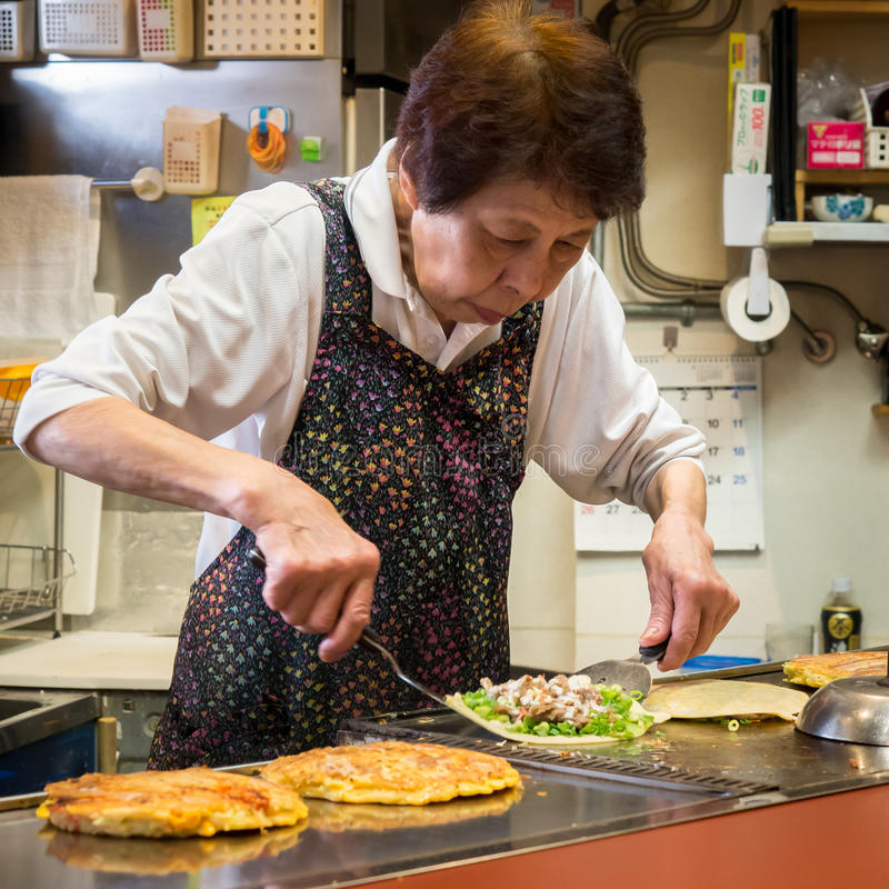 Japanese Lady Making Okonomiyaki Japanese Pancakes stock photography