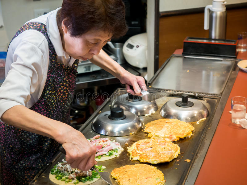 Japanese Lady Making Okonomiyaki Japanese Pancakes royalty free stock image