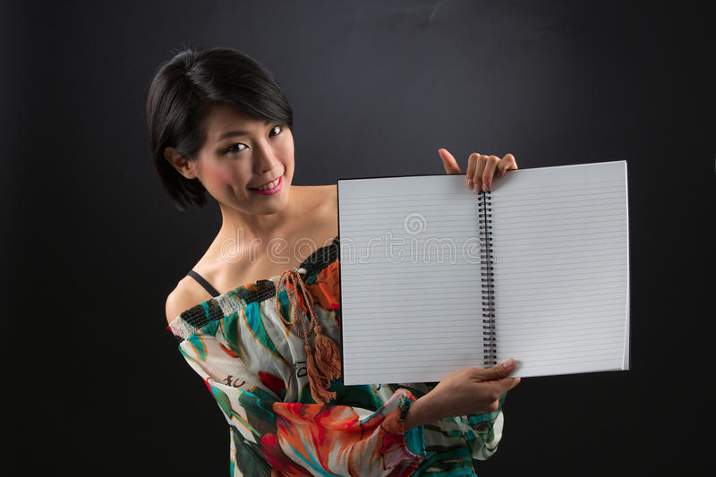 Japanese lady with open blank book. Oriental young woman showing blank pages and rules lines in an open book with black background stock image