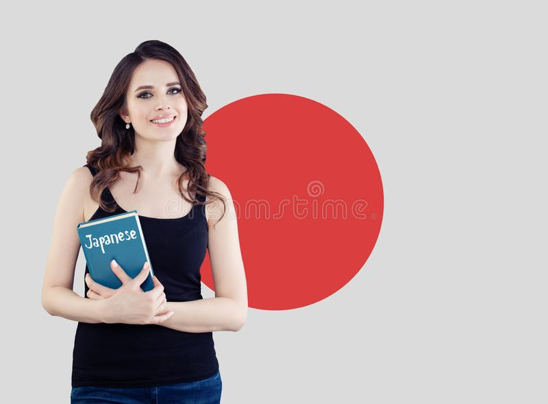 Japanese language school concept. Beautiful brunette woman student with book on the Japan flag background royalty free stock image