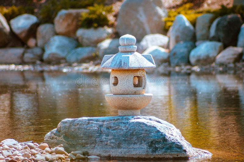 Japanese lantern statue stands alone on a peninsula in the japanese gardens royalty free stock photos