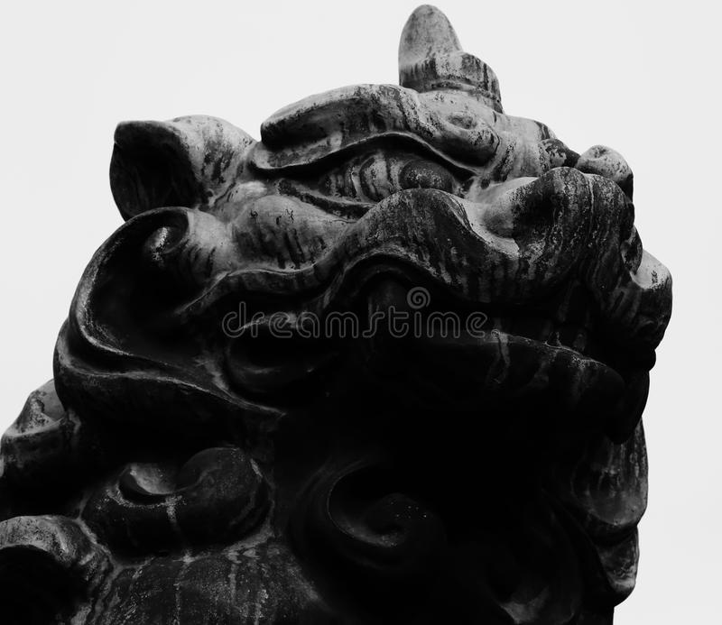 The japanese lion. Shot in black and white, detail on an sculpture representing a lion, placed on a buddhist temple, set in the island of Miyajima, Hiroshima royalty free stock images