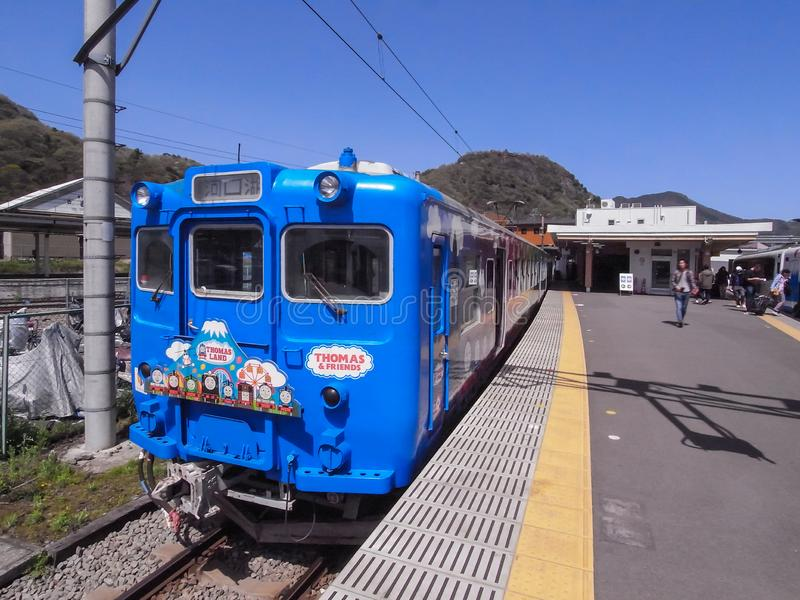 Japanese local blue train in the station of Kawaguchi lake with cute drawing of Thomas Land characters in the front head stock photos