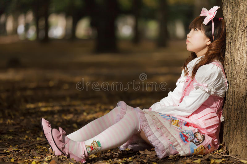 Japanese lolita in park. Thoughtful japanese lolita leaning against tree in park royalty free stock photos