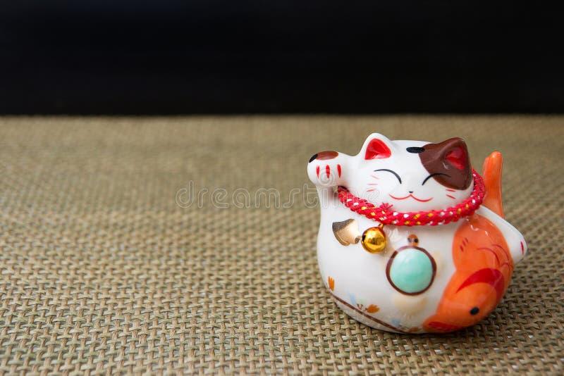Japanese lucky cat maneki-neko on wattled fabric stock images