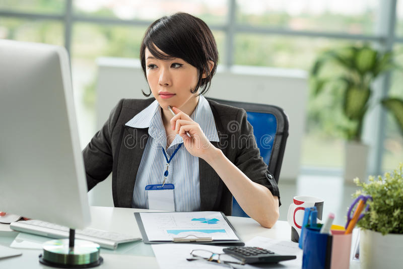 Japanese manager. Reading something on the monitor in the office royalty free stock photos