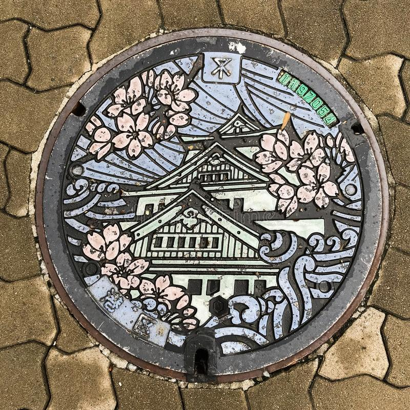 Osaka, Japan: sewer cap / manhole cover / hatch, Japanese language means Osaka royalty free stock image