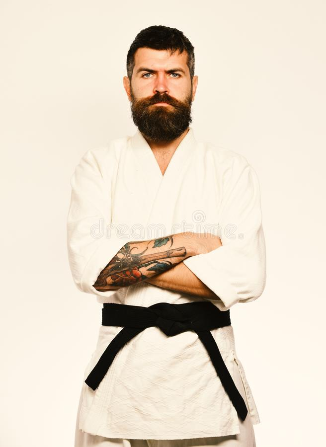 Japanese martial arts concept. Taekwondo master with black belt. Holds arms crossed. Karate man with serious face in uniform. Man with beard in white kimono on stock photos