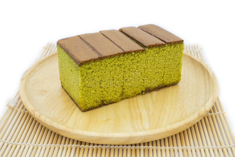 Japanese Matcha green tea cake cheesecake on wooden plate and traditional mat. Isolated white background stock images