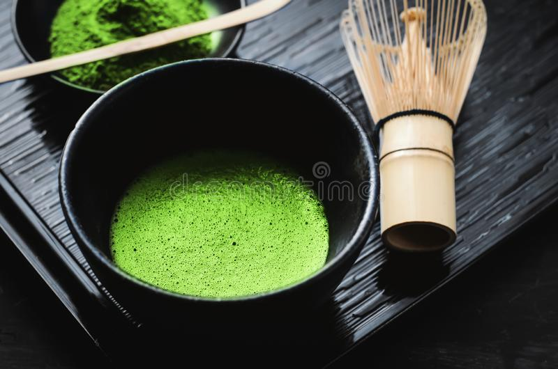 Japanese matcha green tea at homemade clay bowl with bamboo whisk royalty free stock images