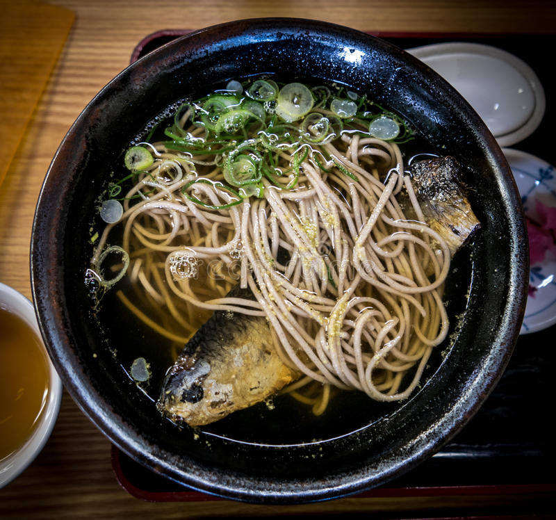 Japanese meal, hot soba noodles with herring fish. stock photo