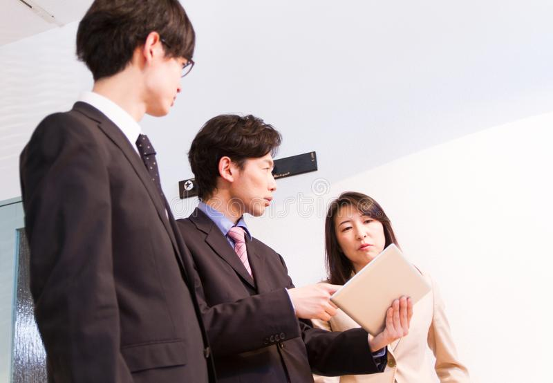 Japanese business person talking about internet contents, using tablet device. Japanese men and woman, talking at team meeting, in front of tablet device stock photo