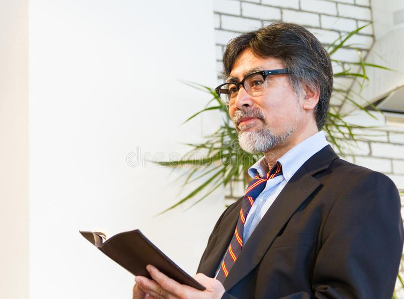 Japanese middle-aged man in suit reading book. Waring glass, with beard royalty free stock photo
