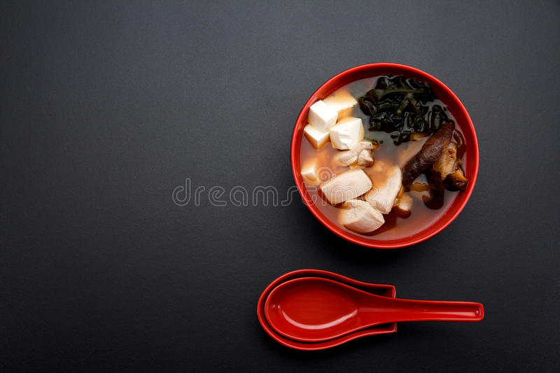 Japanese miso soup on a red bowl and spoon royalty free stock photos