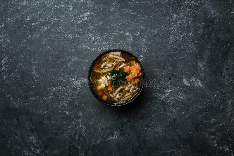 Japanese miso soup with tofu and salmon in a black bowl on a vintage colored background. Vertical view from above stock images