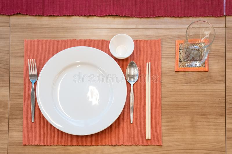Japanese modern applied dining room style with eastern dish, fork, spoon, napkin and glass on the table stock photography
