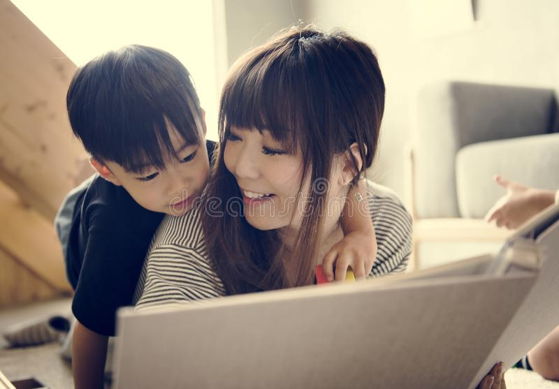 Japanese mother and son watching family photo album in living room royalty free stock photos