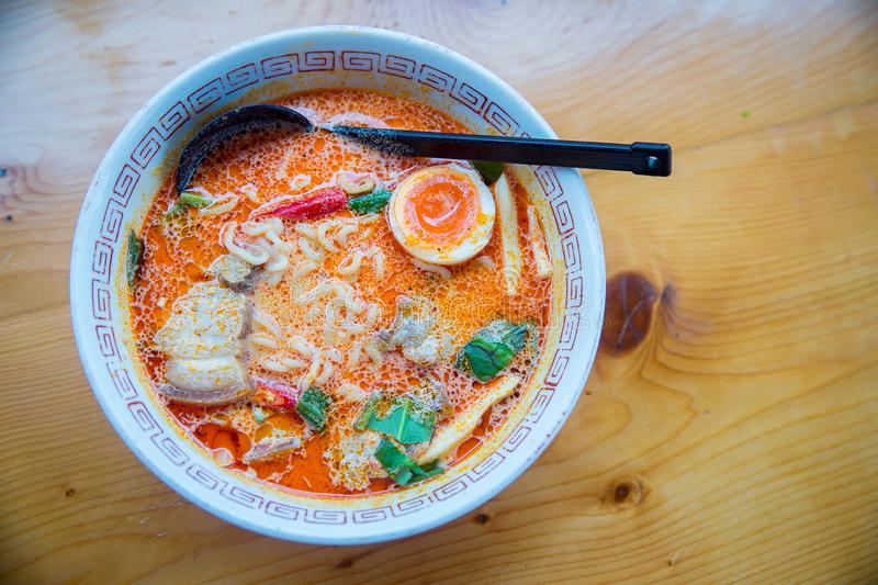 Japanese noodles soul and spicy soup, Udong Ton Yum Kung. fusion food from thai and japanese food. Yummy spicy ramen japanese culture food. image for menu list stock photos