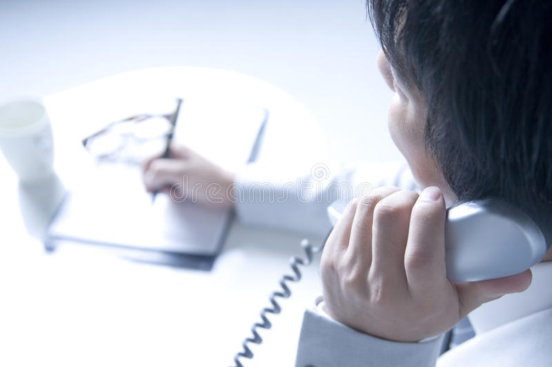 Japanese office worker. BUSINESS IMAGE-close-up shot of a man calling to his business connection and taking a memo royalty free stock images