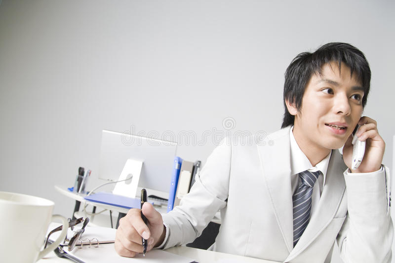 Japanese office worker. BUSINESS IMAGE-close-up shot of a man calling to his business connection and taking a memo stock photo