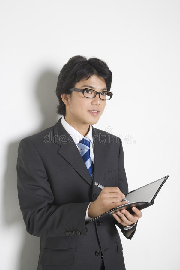 Japanese office worker. BUSINESS IMAGE-a businessman taking memos royalty free stock photo