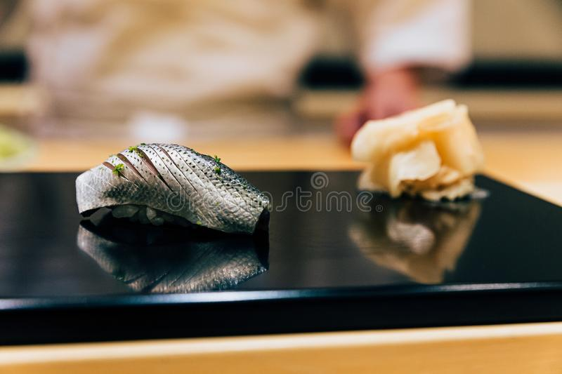 Japanese Omakase Menu: Saba Sushi Mackerel sprinkle minced Yuzu peel served by hand with pickled ginger on glossy black plate. stock photo