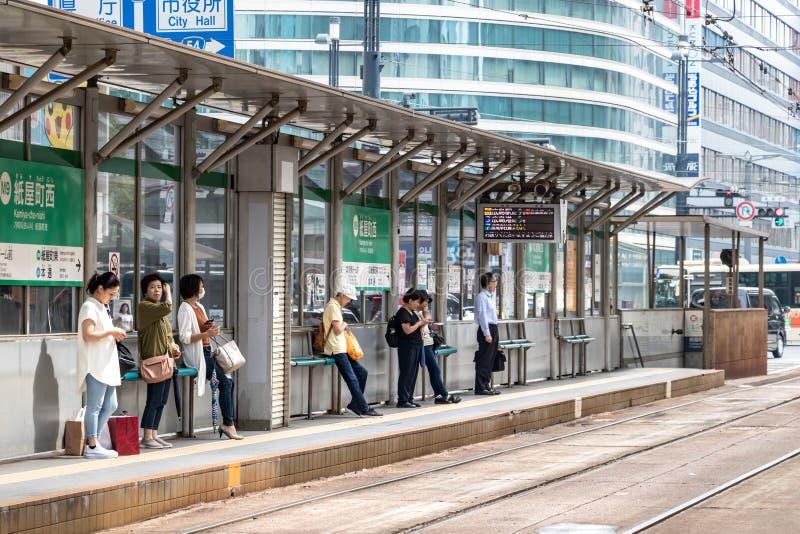Japanese passengers waiting the tram at the Kamiyacho-nishi tram station in Hiroshima. royalty free stock photo
