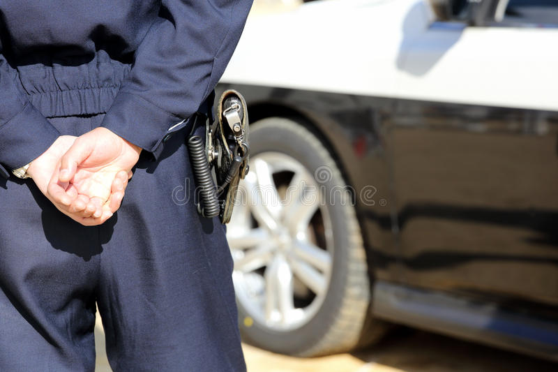 Japanese police officer with patrol car. Back view of Japanese police officer with patrol car royalty free stock photos