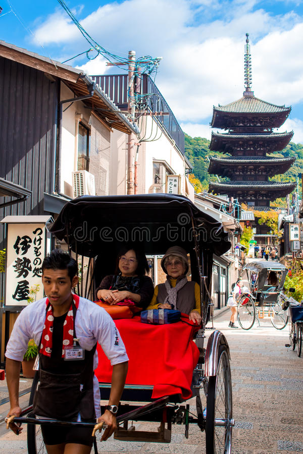 Japanese pulled rickshaws called jinrikisha, carrying tourists through the old streets of Kyoto royalty free stock image
