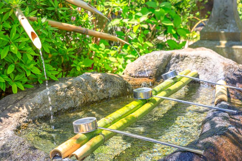 Japanese purification fountain. Close up of Japanese bamboo fountain and ladles used for washing hands. Purification fountain with ladles at a Buddhist temple royalty free stock photo