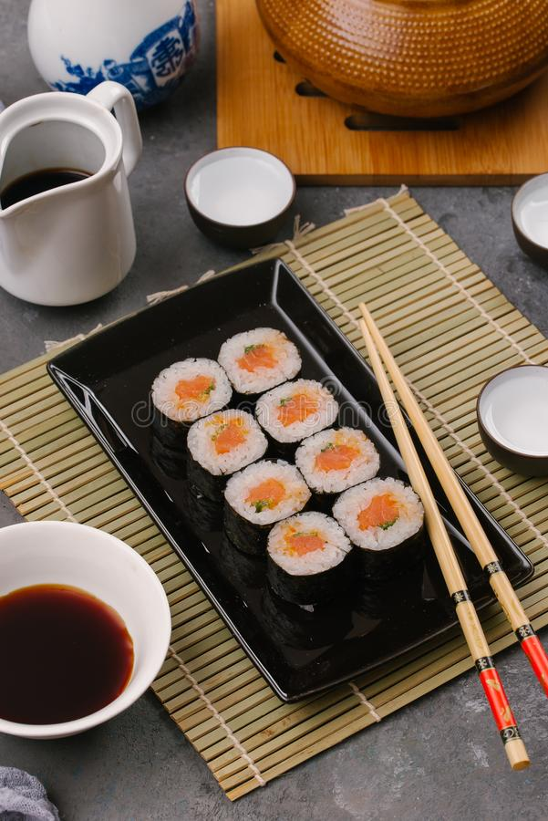 Japanese restaurant, sushi roll on black slate plate. Set for one person with chopsticks, ginger, soy, top view, copy stock photography