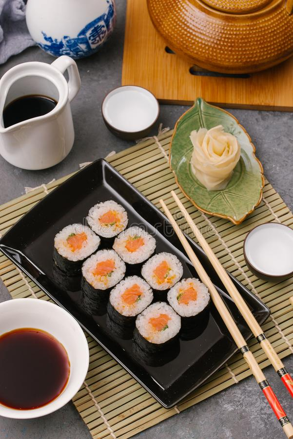 Japanese restaurant, sushi roll on black slate plate. Set for one person with chopsticks, ginger, soy, top view, copy. Japanese restaurant, sushi roll on black stock photos