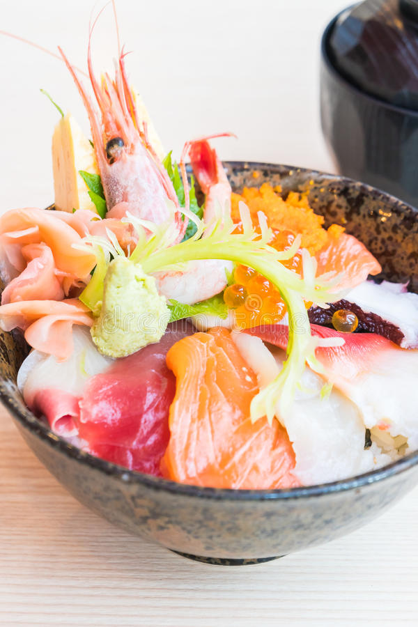 Japanese rice bowl with sashimi seafood on top. Selective focus point royalty free stock image